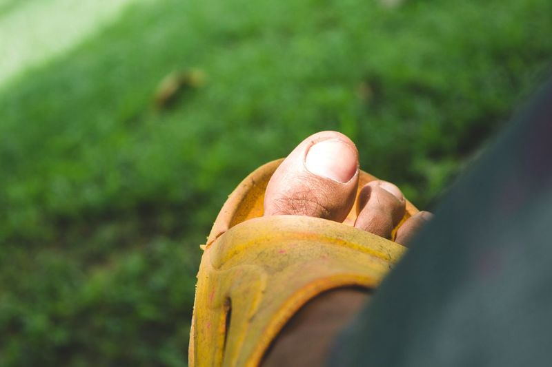Low Section Of Man Wearing Yellow Slipper
