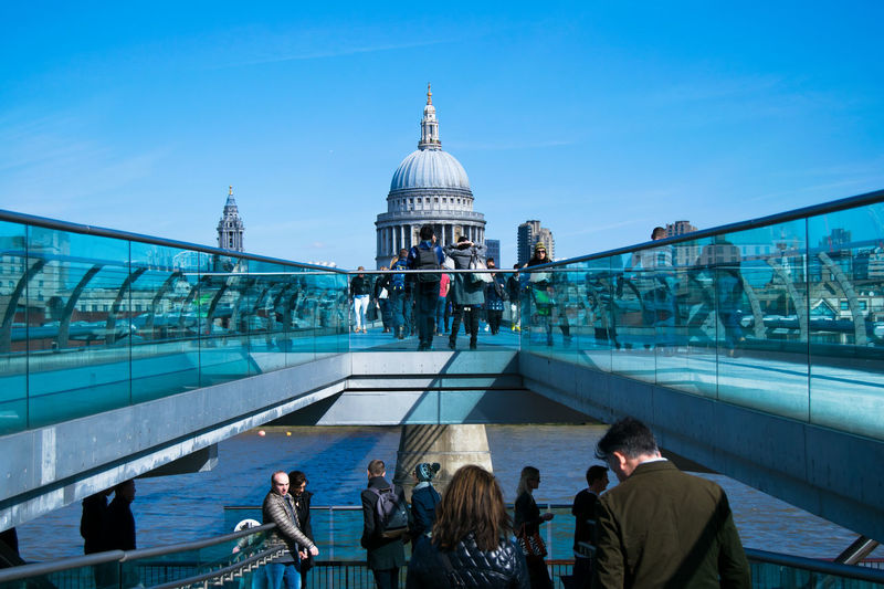 People On London Millennium Footbridge In Front Of St Paul Cathedral Against Sky