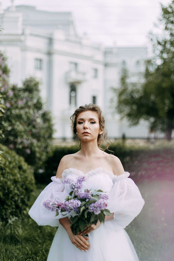 A beautiful delicate elegant young woman bride in a wedding dress walks alone in a spring park