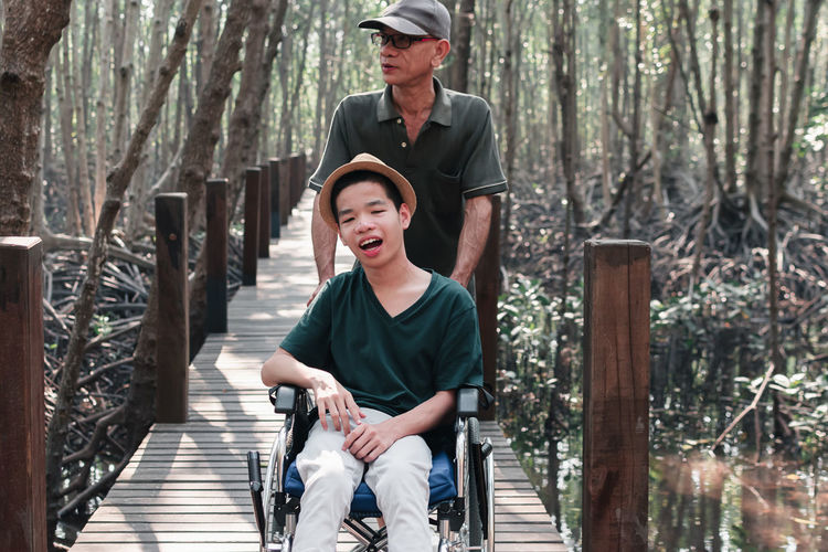 Man carrying boy on wheelchair amidst trees