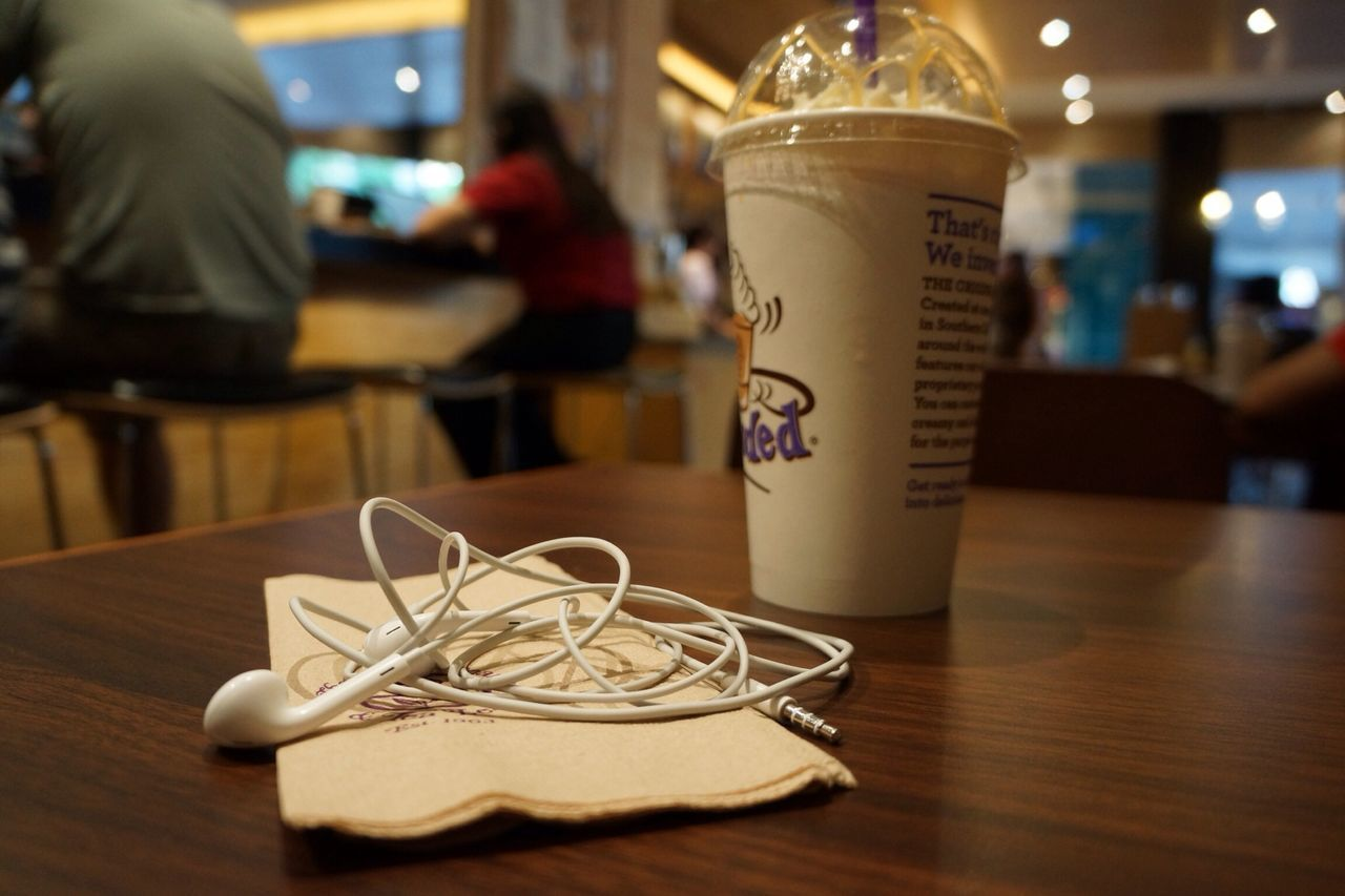 Headphones And Coffee In Disposable Cup On Table At Cafe