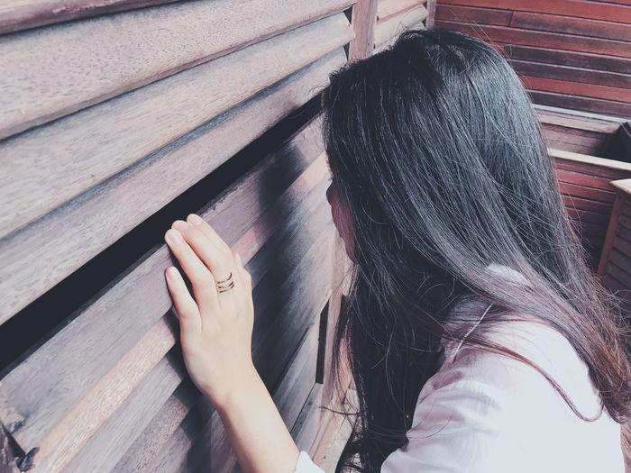 Side view of young woman peeking through wooden window shutters