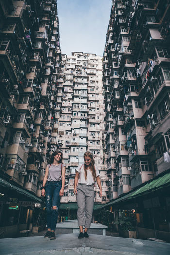Full length of woman with modern buildings in city