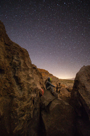 Rear view of person on rock at night
