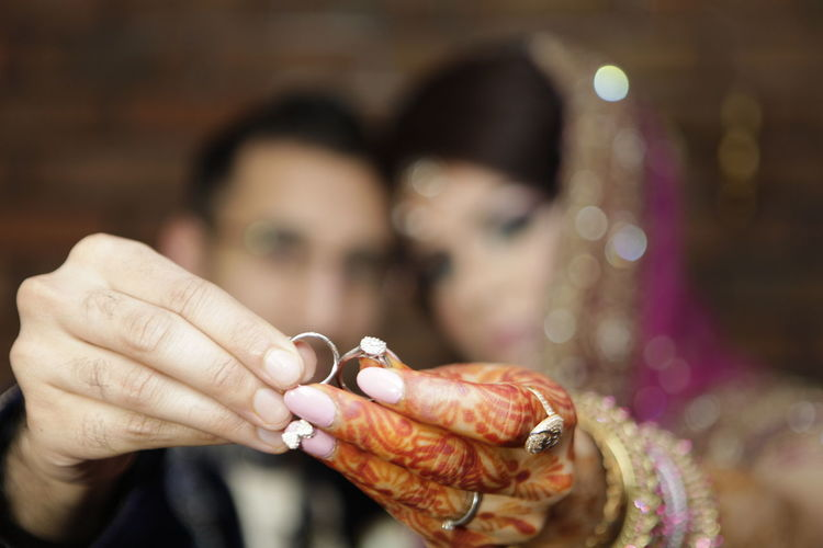 Close-Up Of Couple Holding Wedding Rings In Hand