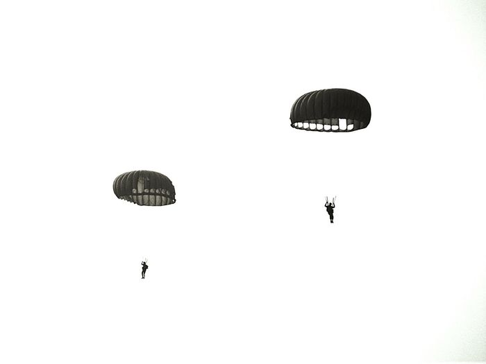 Low angle view of men with parachutes against clear sky