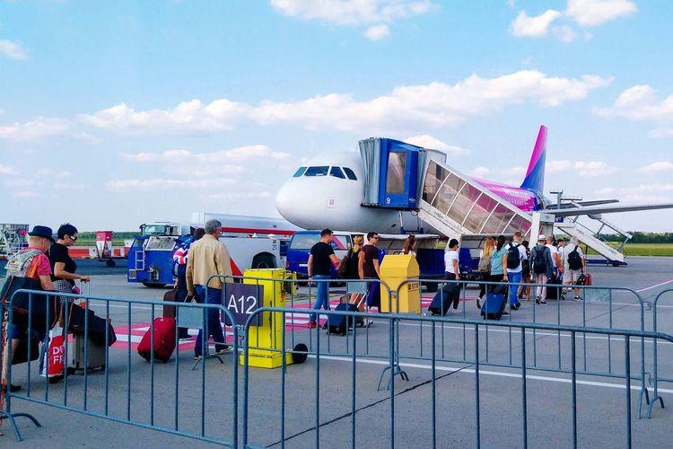 Group of people on airport runway against sky