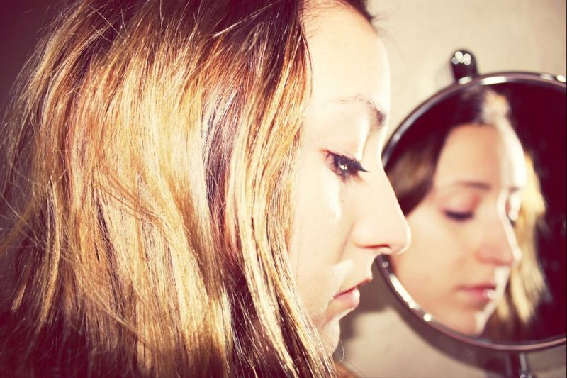 A young woman looks at herself in a mirror