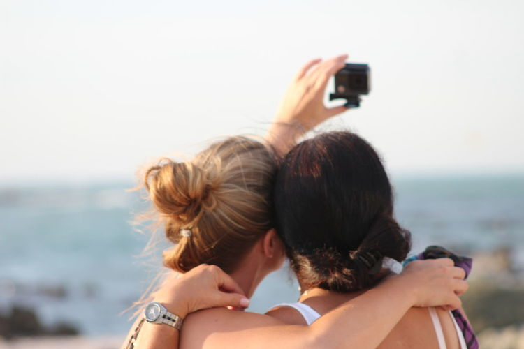 Rear View Of Female Friends Taking Selfie With Camera Against Sky