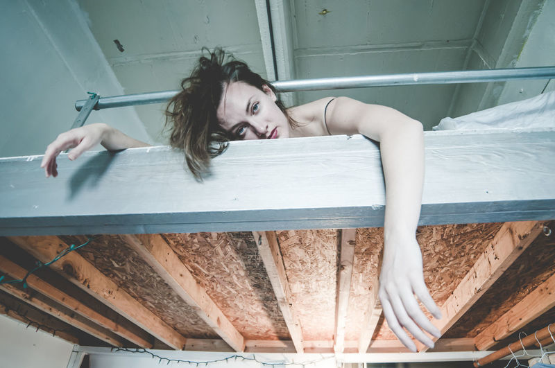 Low angle portrait of woman lying on bed