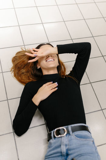 Young woman using phone while standing on tiled floor