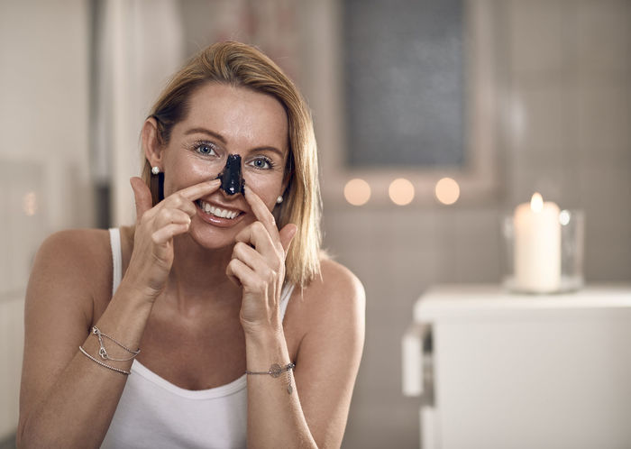 Middle-aged woman applying a mask to her nose Woman Anti-aging Applying Beautiful Woman Blond Hair Cosmetics Face Mask Focus On Foreground Headshot Indoors  Looking At Camera Middle-aged Moisturizer Nose One Person One Woman Only Portrait