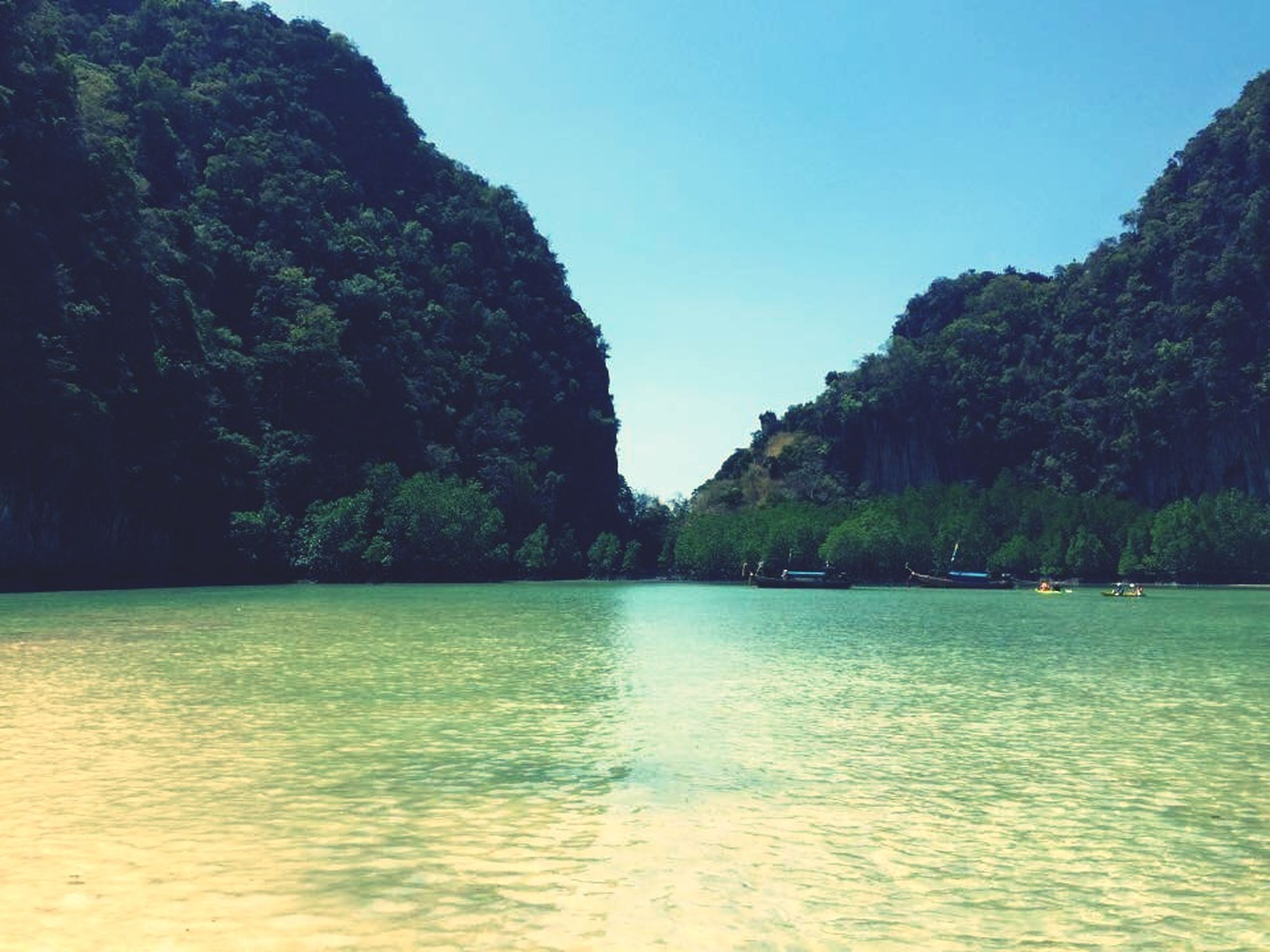 water, tranquil scene, tranquility, scenics, tree, beauty in nature, waterfront, clear sky, mountain, nature, blue, sea, idyllic, lake, rippled, sky, day, non-urban scene, calm, copy space