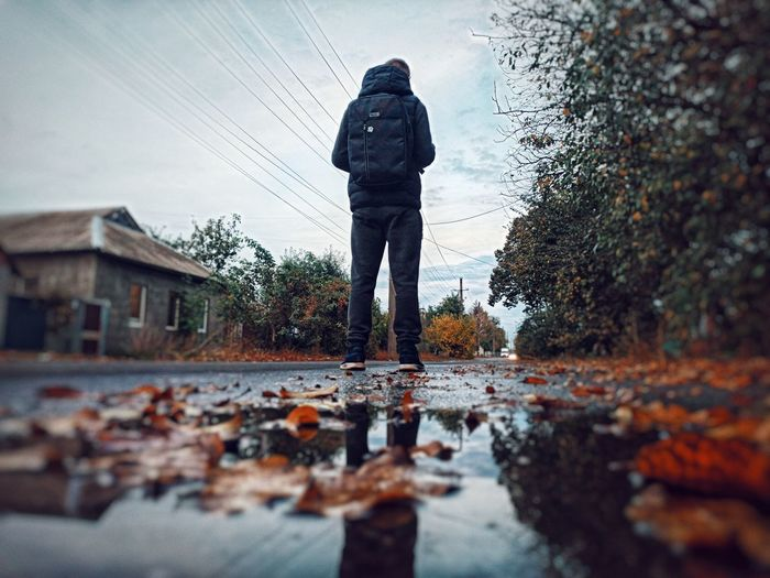 Rear view of man standing on puddle during rainy season