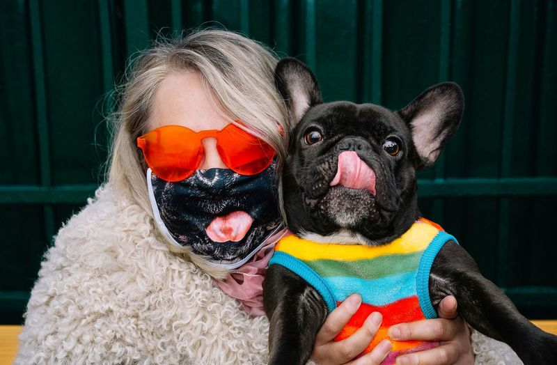 Portrait of woman with mask holding small french bulldog dog