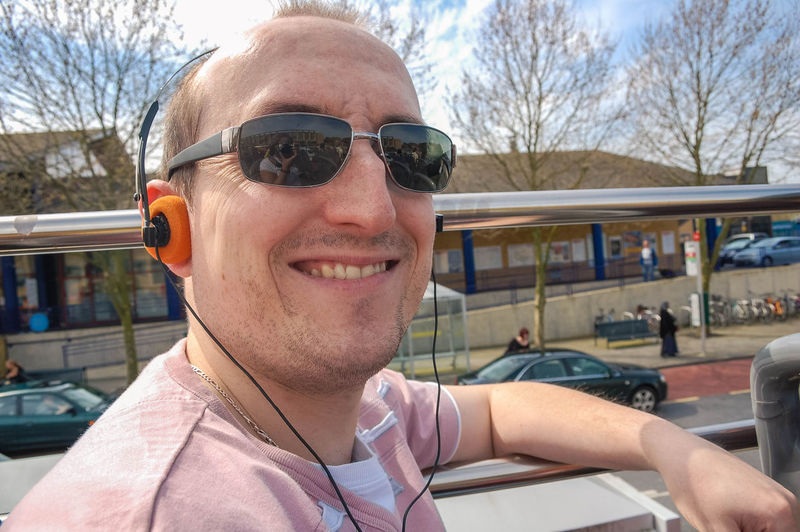 A man wears headphones to listen to commentary on a tour bus ride around Oxford. Adult Bus Tour Happy Headphone Headshot Man One Man Only One Person Outdoors Portrait Shades Smile Smiling Stubble Sunglasses T-shirt Unshaven