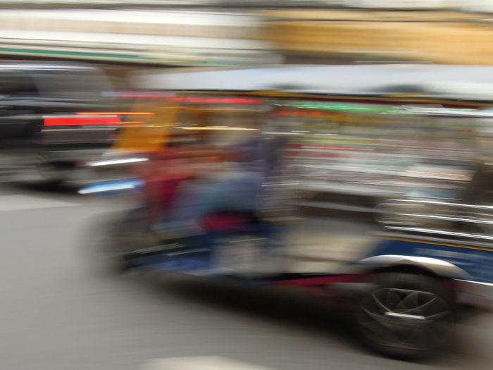 Blurred motion of people riding motorcycle on road in city