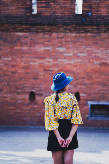 Rear view of woman in hat standing against wall
