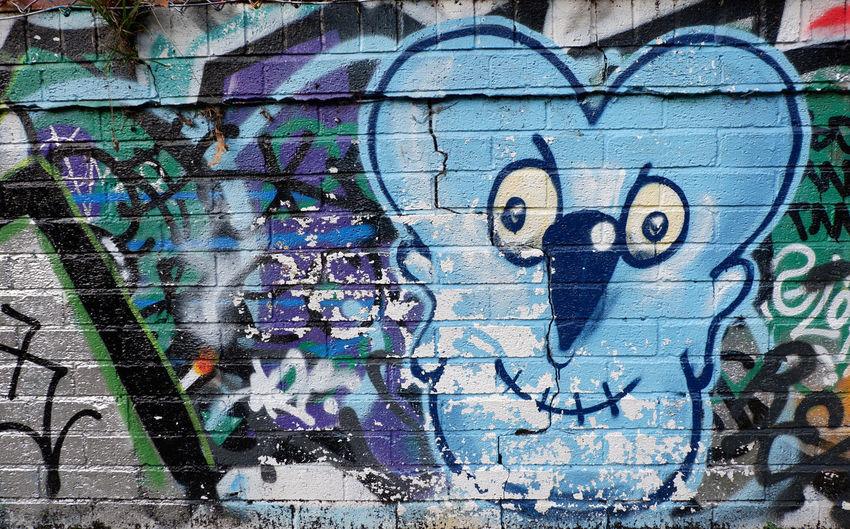 Colourful blue face graffiti on a brick wall along the Regents Canal Brick Wall Colourful Graffiti Paint Regents Canal A Blue Blue Face Defaced Graffiti Art