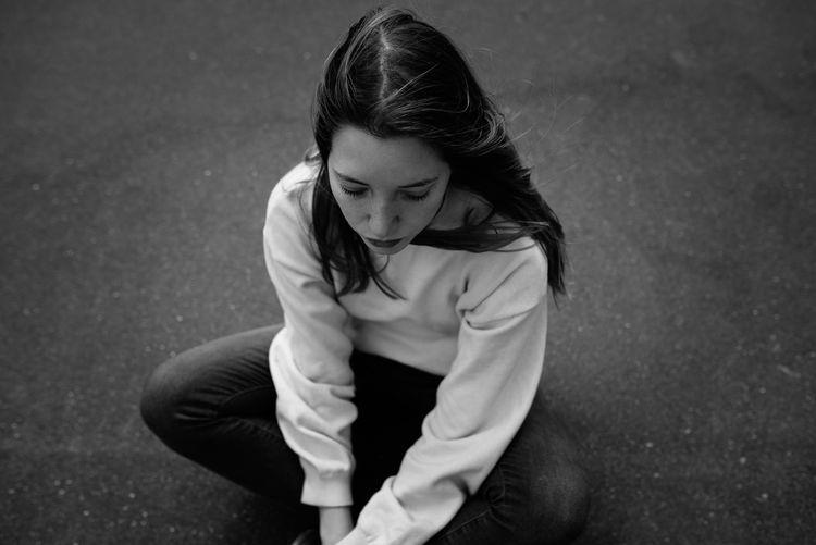 High angle view of teenage girl sitting on the ground
