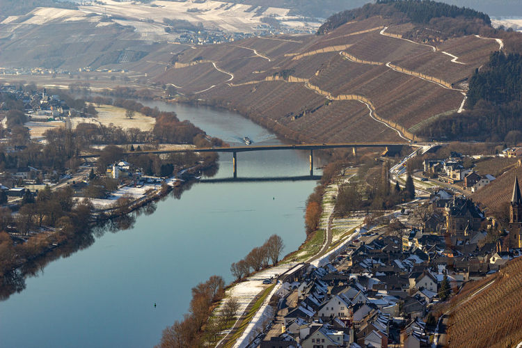 View on the valley of the river moselle and the wine villages mülheim and lieser in winter with snow
