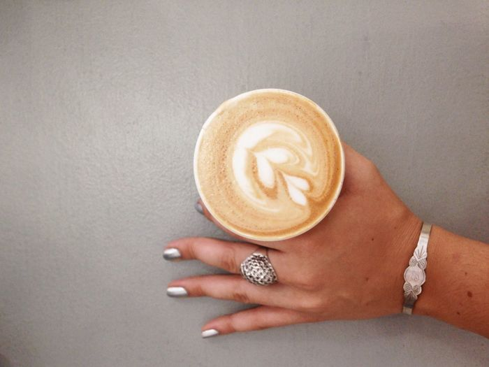 Cropped Image Of Woman Holding Cappuccino On Gray Table