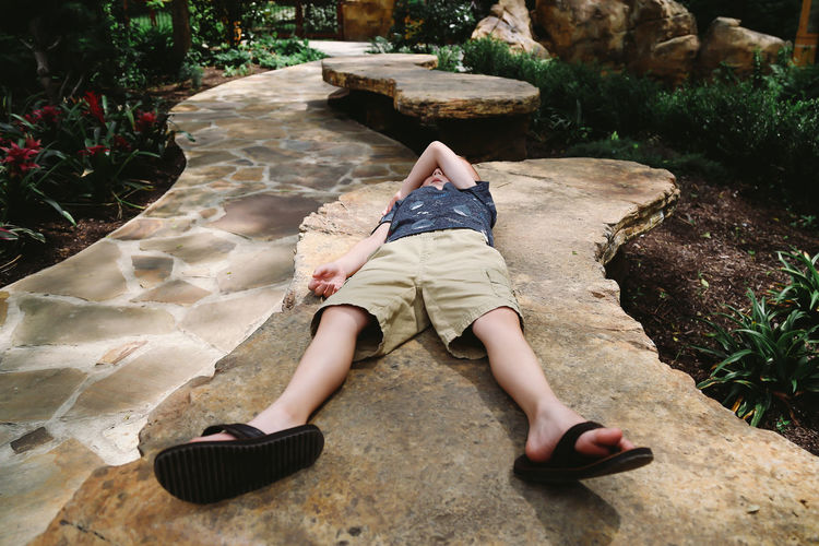 Child Laying Down on Rock Resting Under the Sun in the Summertime One Person Real People Leisure Activity Lifestyles Full Length Nature High Angle View Rock Day Casual Clothing Relaxation Child Childhood Boy Kids Boyhood Sunset Summertime Zoo Fun Summer Fun Nashville Summer Vacation Vacations