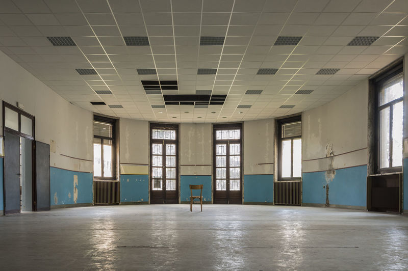 Internal room of old and abandoned devastated school, ready for renovation Arcade Architectural Column Architecture Building Built Structure Ceiling Day Domestic Room Empty Entrance Flooring Indoors  Modern Office People Reflection Warehouse Window