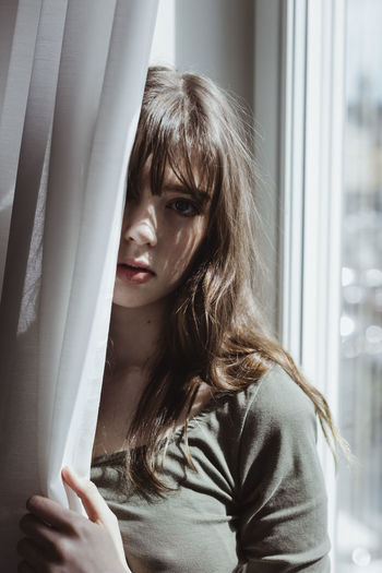 Portrait of young woman looking through window at home