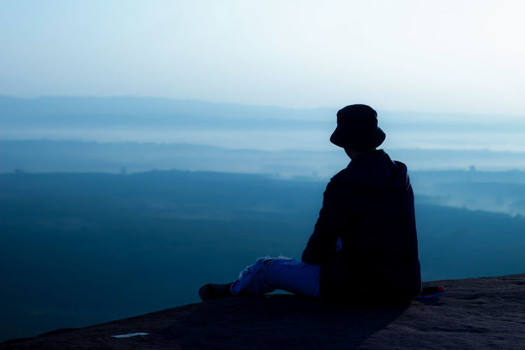 Man sitting and watching the sunrise in the morning on the cliff