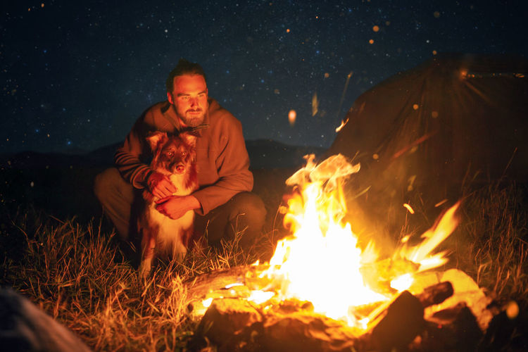 Man with dog sitting by campfire at night
