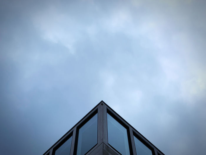 Low angle view of windows of a building against sky