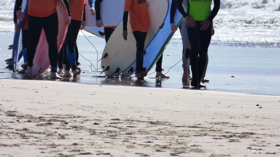 Low Section Of People With Surfboards Walking At Beach