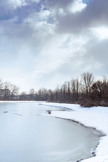 Scenic view of frozen lake against sky during winter