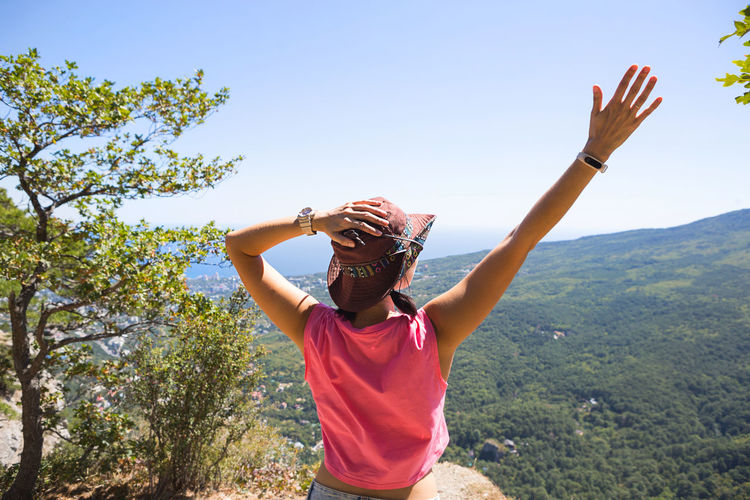 Woman in a hat looks at the panoramic view from the mountain to the sea and