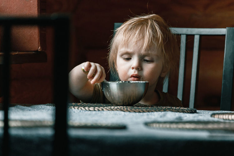 Portrait of cute baby in bowl on table