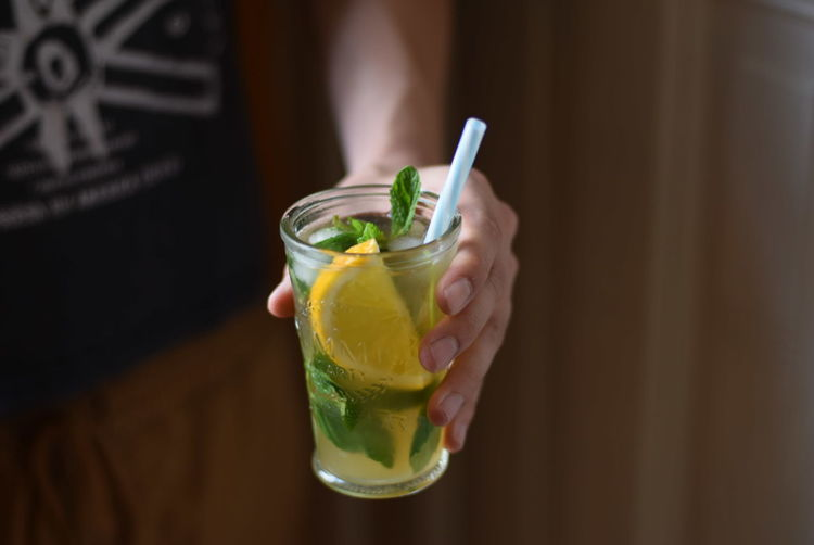 Close-Up Of Person Holding Lemon Beverage