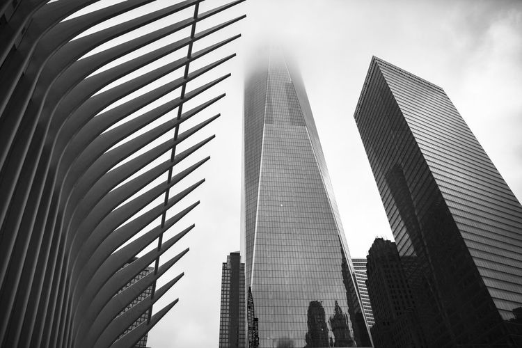 Low angle view of one world trade center amidst modern buildings against sky