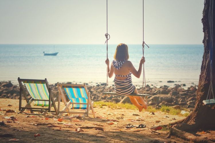 Rear view of woman swinging on swing at beach against sky