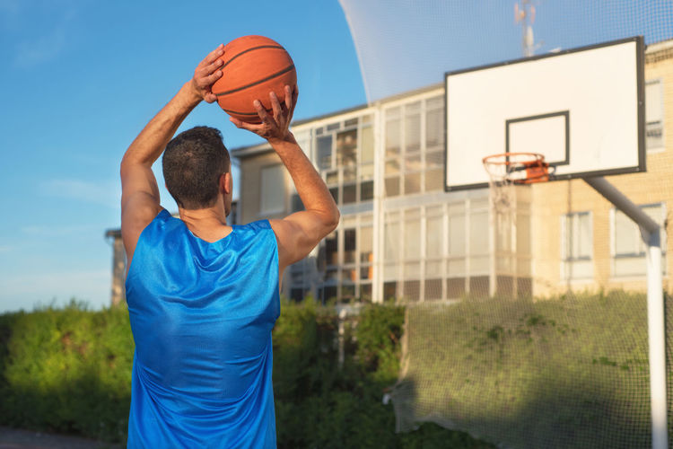 Low angle view of man playing basketball against blue sky
