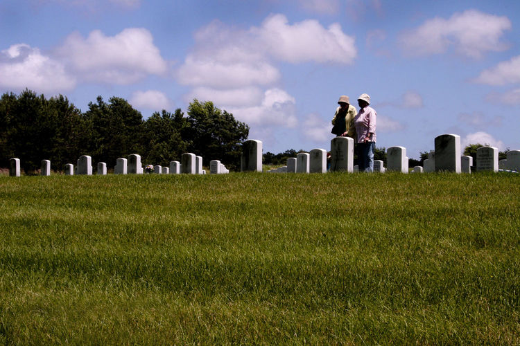 Women standing by gravestones at cemetery against cloudy sky