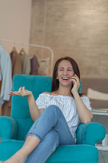 Happy mature woman talking on mobile phone at home