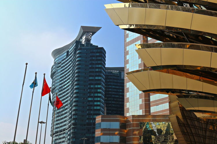 Low angle view of flags by modern buildings in city against clear sky