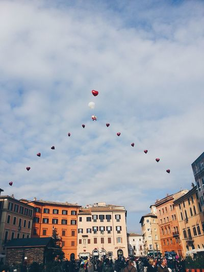 Low angle view of heart shape balloons over city at valentine day