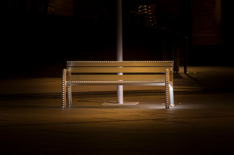 Empty bench on table at night