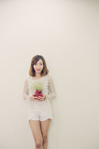 Portrait Of Woman With Flowers Standing Against White Background