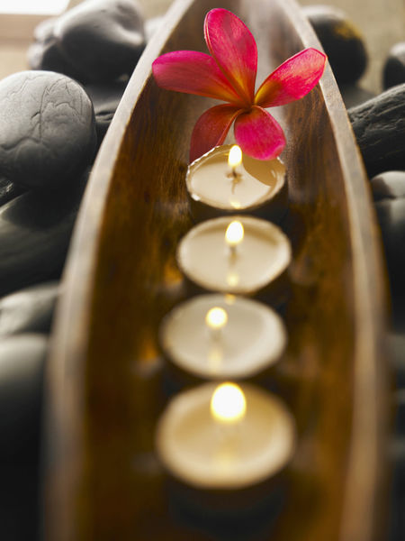 Lit tealight candles with flower arranged in wooden tray with stone background Frangipani Aromatherapy Beauty Spa Candle Close-up Day Flame Flower Freshness Illuminated Indoors  No People Pebble Selective Focus Spa Stone Table Tea Light Tea Lights