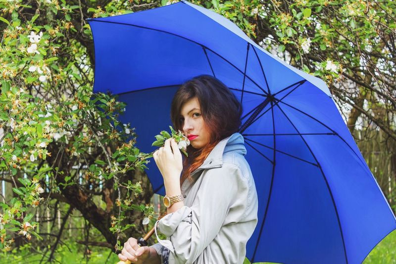 Woman Holding Umbrella While Smelling Plant