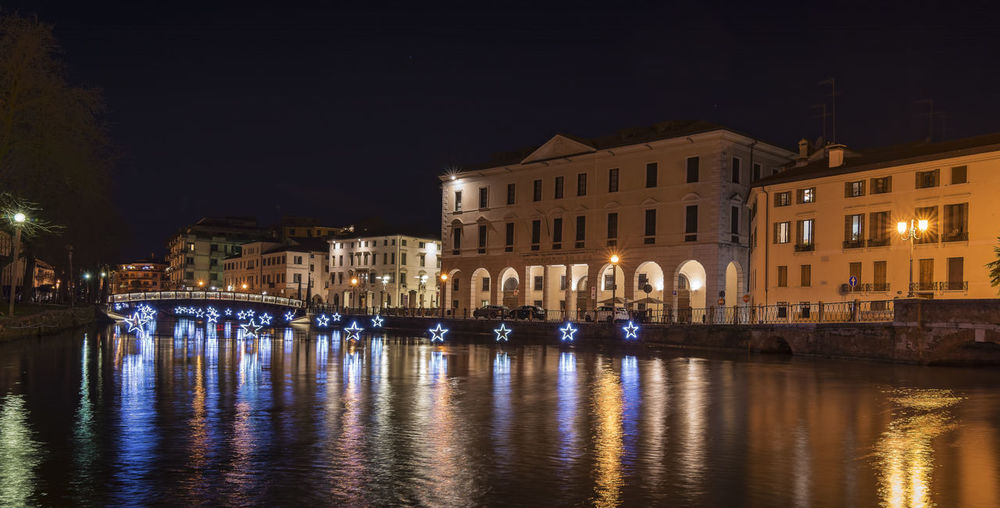 Treviso by night during christmas. university bridge and the light stars reflect on the river sile.