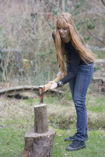 Portrait of young woman chopping wood